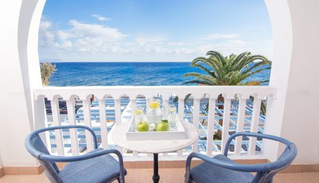 Two chairs, one table with fruits and refreshments on the balcony overlooking Kamari Beach.